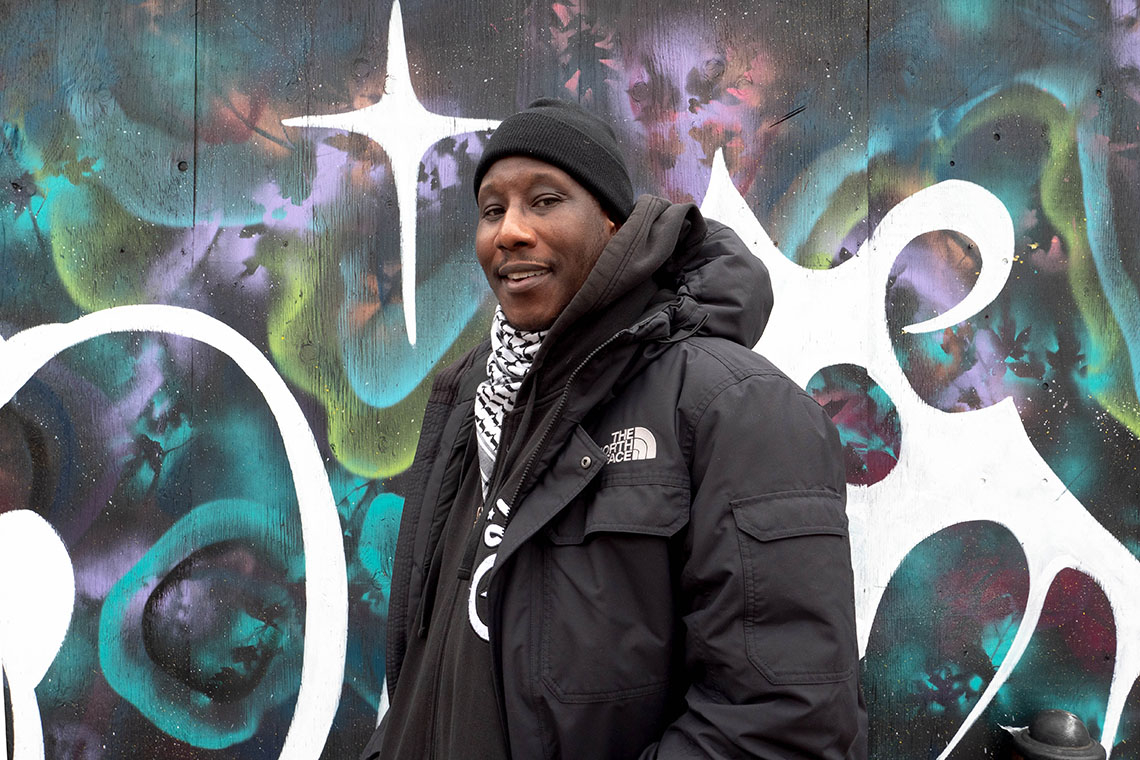 photo of Marcus Singleton standing in front of a graffitti wall