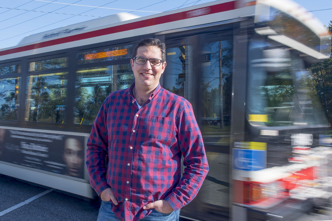 Steven Farber outside with a bus passing behind him