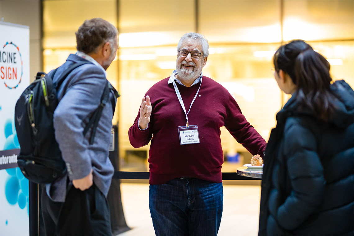 Michael Sefton speaks with two attendees at the Medicine By Design symposium at the Mars Discovery District