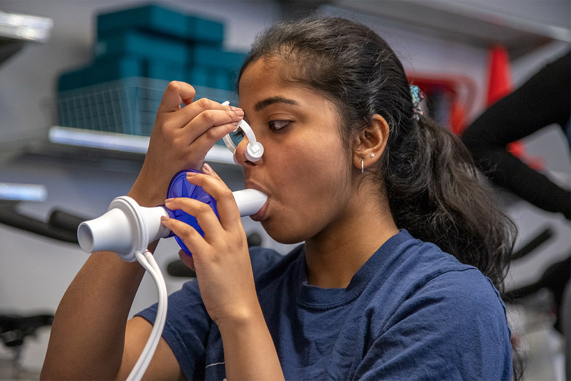 A student breathes into a machine that tests her respiratory levels