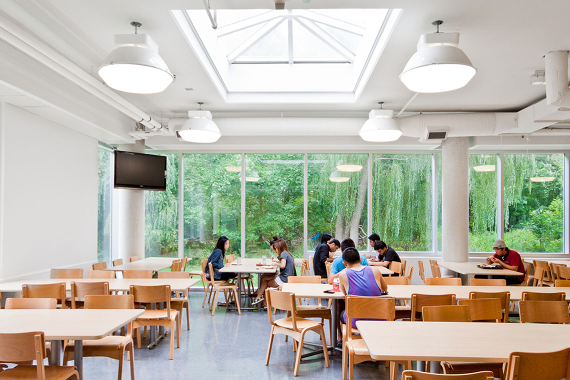 Students eat in a cafeteria at the University of Toronto Mississauga campus with green foliage visible in the background