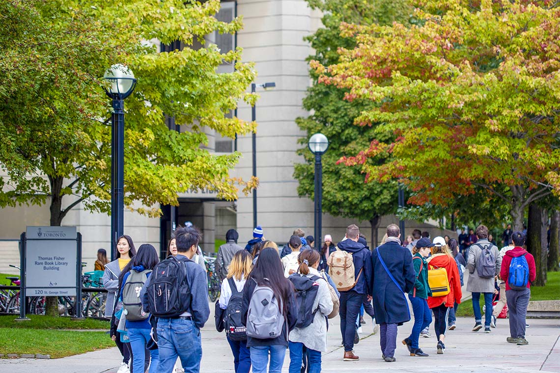 Many students walking in front of Roberts Library with fall foliage visible