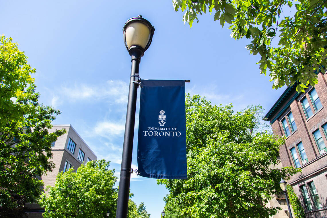 A U of T banner hangs from a lamp post on campus
