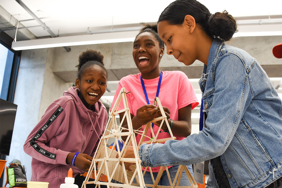 3 young women work on a structure made from popsicle sticks and glue while laughing