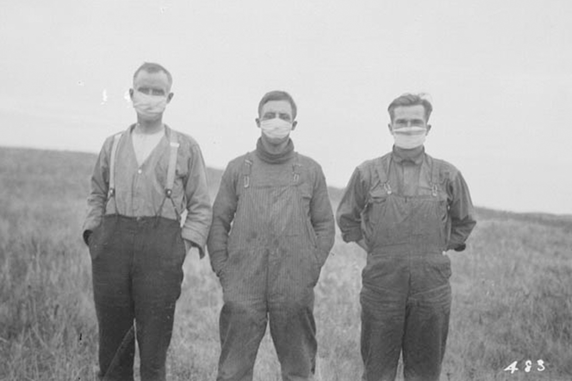Three men stand in a field in alberta wearing gauze masks
