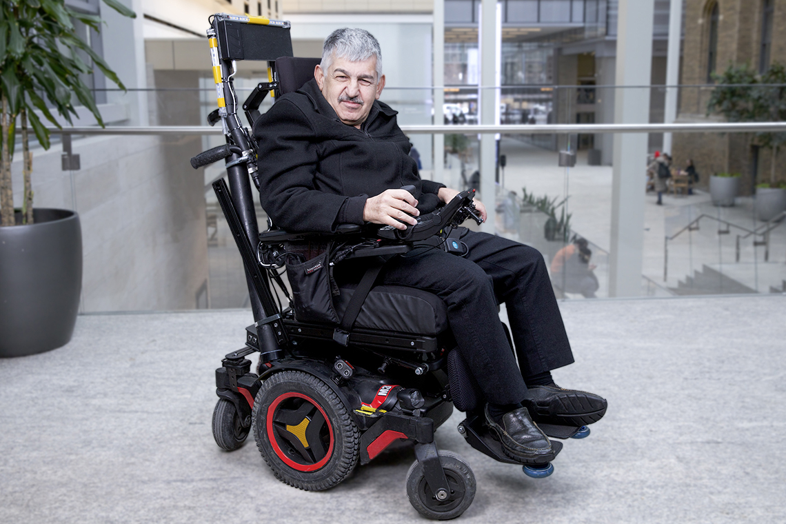 Braze Mobility smart wheelchair sensors are attached to the back and footrests of a smiling man's powered wheelchair