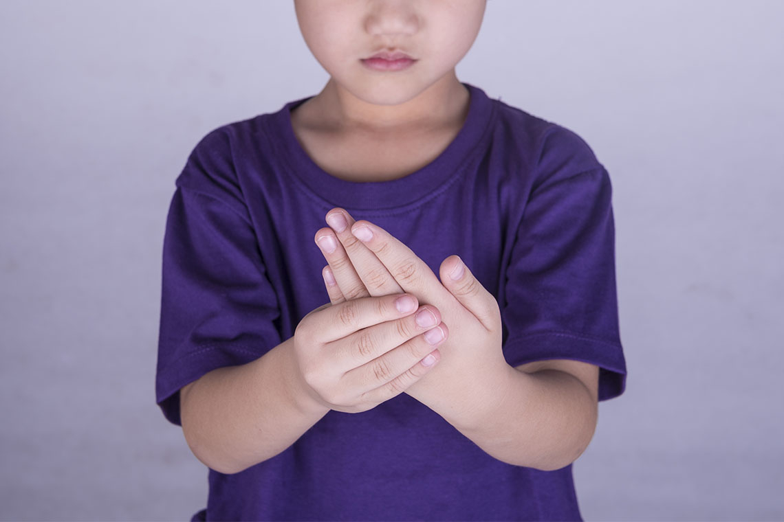 photo of boy grasping fingers