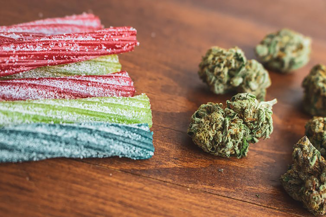 Photo of cannabis candy and cannabis buds sitting on a table