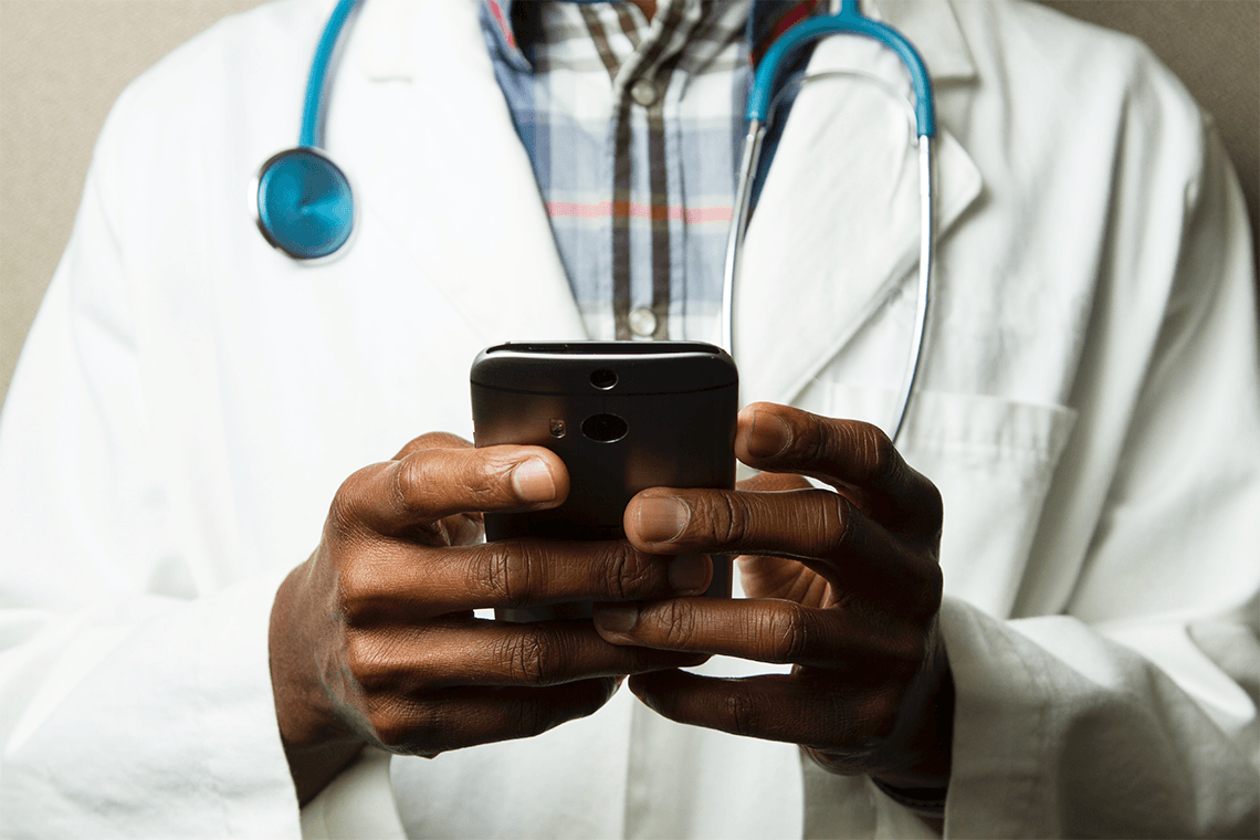 A man wearing a white coat and stethoscope types on a smartphone, representing Hypercare's health-care communications app.