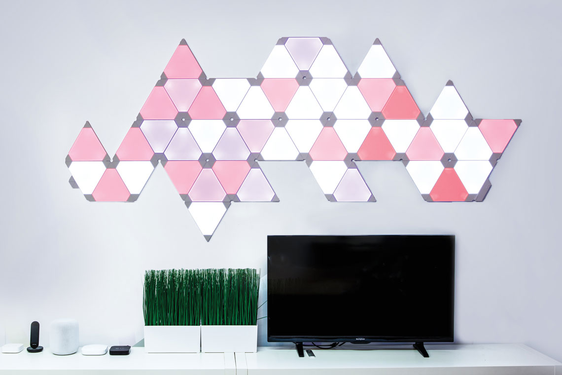 An array of Nanoleaf Canvas sustainable smart lighting squares forms a geometric pattern on a living room wall