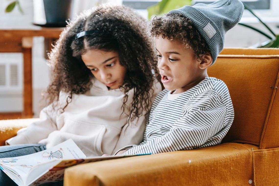 two young Black children read a picture book