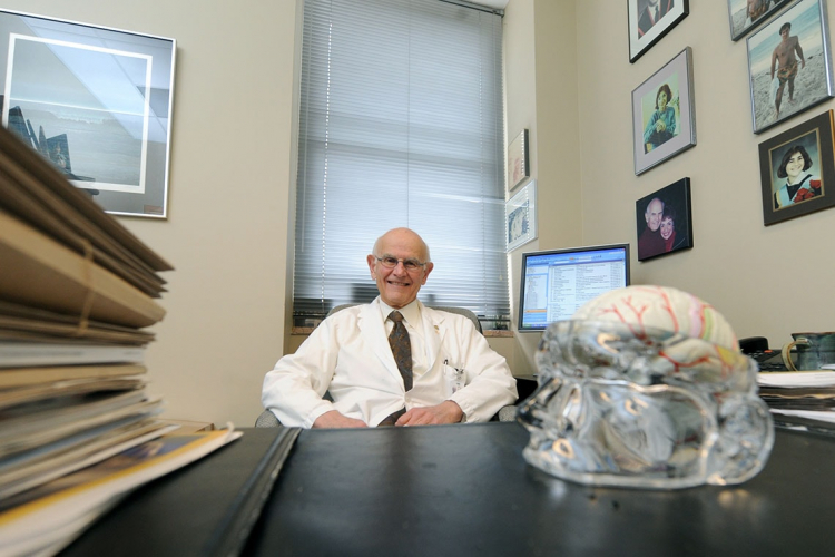 Photo of Dr. Charles Tator at his desk