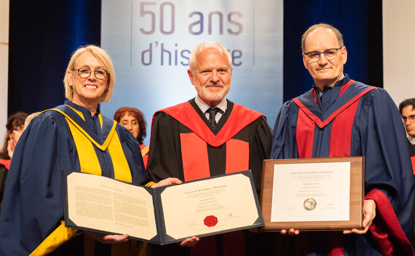 Photo of Professor Normand Labrie holding honorary degree, flanked by University of Quebec at Rimouski's president and rector
