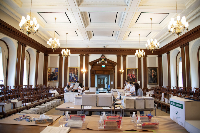 volunteers stuff degrees into envelopes at simcoe hall