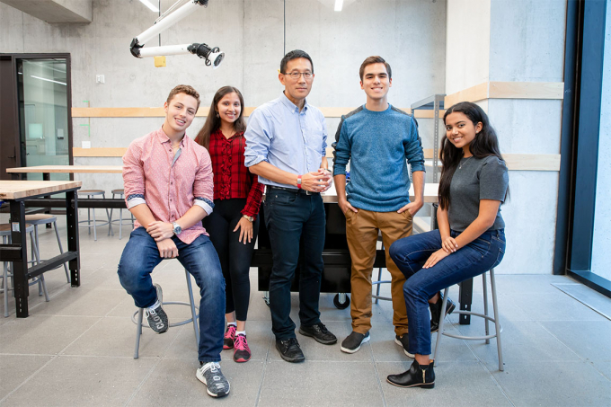 Chris Yip poses in an engineering lab with four Pearson Scholars