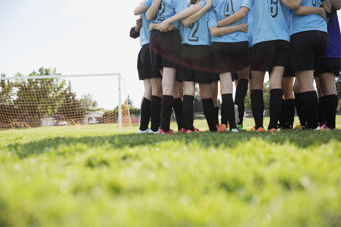 A group of young female soccer players in a huddle