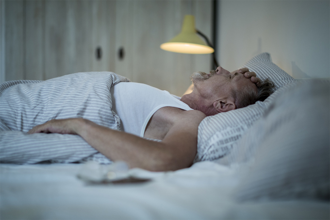an elderly man lies in bed trying to go to sleep