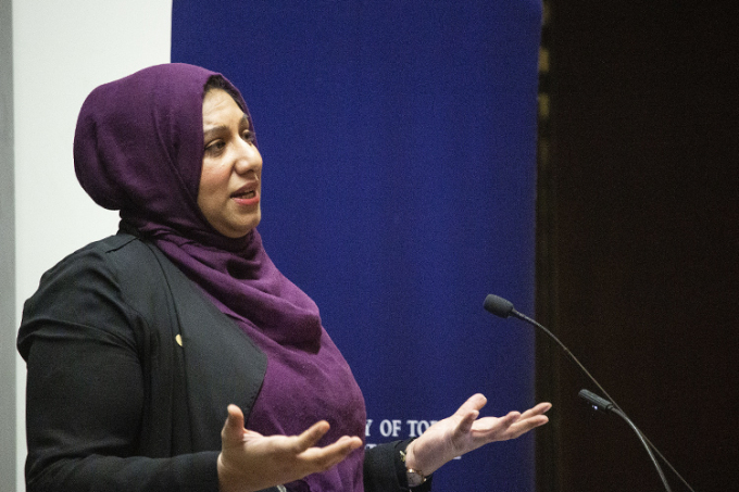 Ausma Malik stands in front of a microphone