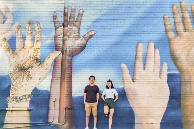 Weiwei Li and Catherine Chan stnad in front of a large mural on a wall depicting hands of different colours raised up