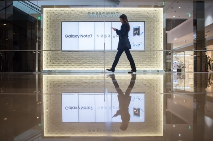 A woman walks in front of an advertisement for a Samsung phone in Korea