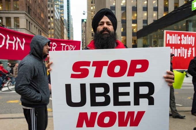 "Toronto taxi driver holds a sign saying ""Stop Uber Now"""