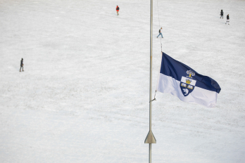 U of T flag at half-mast with a snowy field in the background