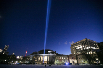 Commemorative light shines against the night sky in front of convocation hall on the National Day of Remembrance 2019