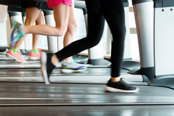 Waist-down photo of people exercising on treadmills