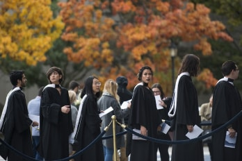 Photo of grads and fall trees