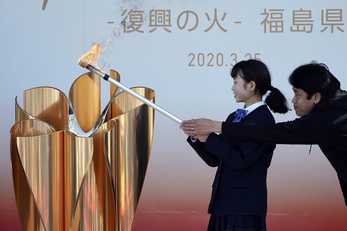 a man and a woman light an olympic cauldron together in tokyo